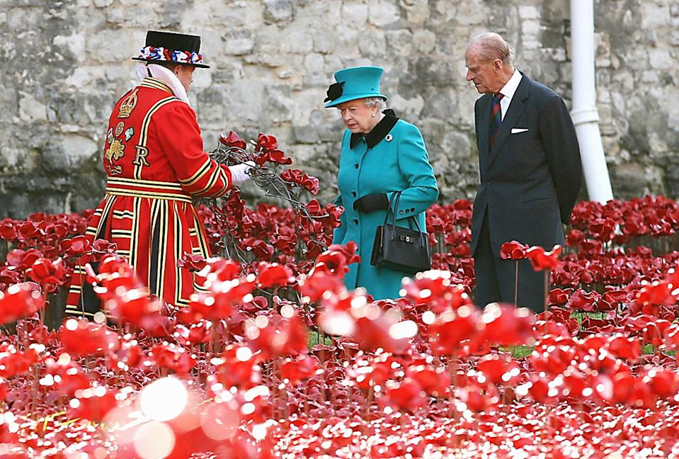 The Queen and the Duke of Edinburgh visiting the poppy field at the Tower of London in 2014 (Picture: PA)