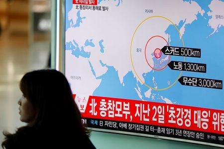 A woman walks past a television broadcasting a news report on North Korea firing ballistic missiles, at a railway station in Seoul, South Korea, March 6, 2017.  REUTERS/Kim Hong-Ji