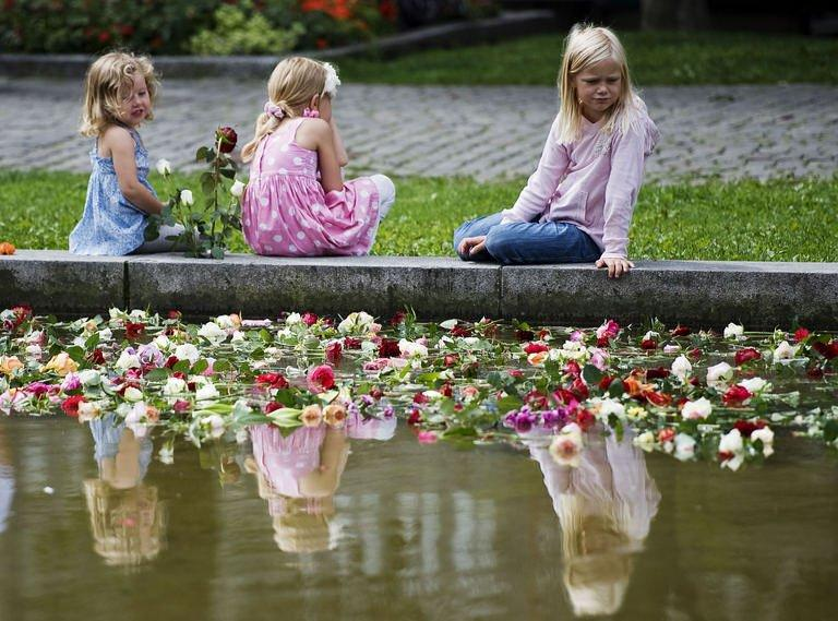 Three young girls sit and look at flowers floating in water in Oslo. Business has never been so good, but the bumper takings are of little comfort to Norway's flower sellers as they struggle to keep pace with the demand from a nation in mourning