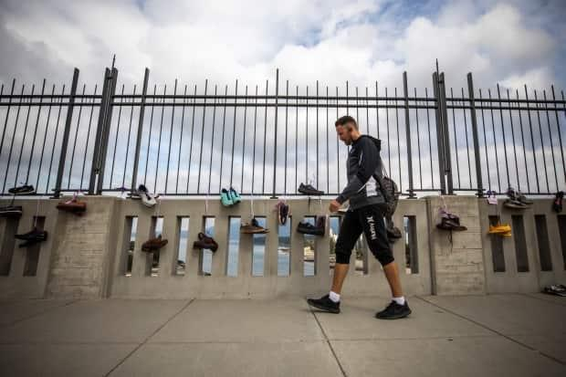 Pairs of shoes representing a life lost to a drug overdose hang on the Burrard Street Bridge in Vancouver on International Overdose Awareness Day, Aug. 31, 2020.   (Ben Nelms/CBC - image credit)