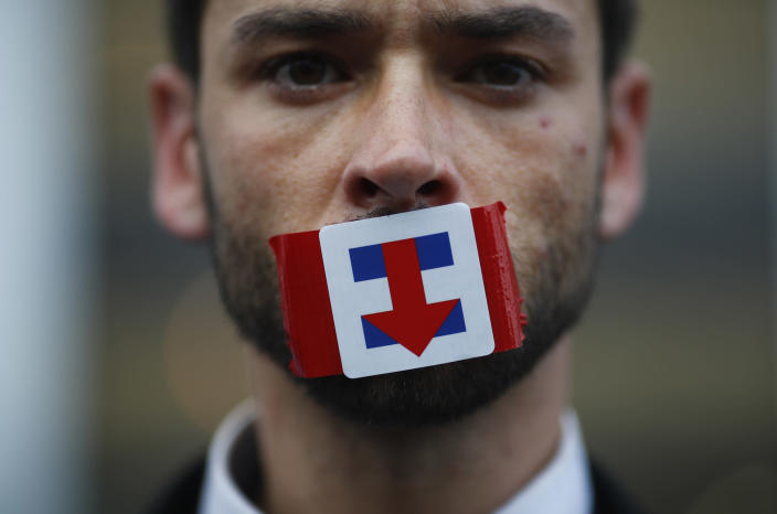 A former Bernie Sanders delegate wears a Hillary Clinton presidential campaign sticker over his mouth as he protests during the third session at the Democratic National Convention in Philadelphia in July 2016. (Photo: Carlos Barria/Reuters)