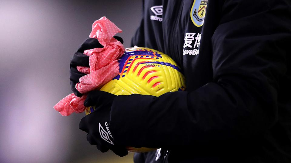 A member of staff cleans a ball during the Premier League match between Burnley and Sheffield United at Turf Moor on December 29, 2020 in Burnley, England. The match will be played without fans, behind closed doors as a Covid-19 precaution. (Photo by Alex Pantling/Getty Images)