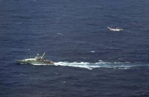 Australian navy boat (L) shadowing a boat (R) believed to be carrying up to 180 asylum-seekers off Indonesia