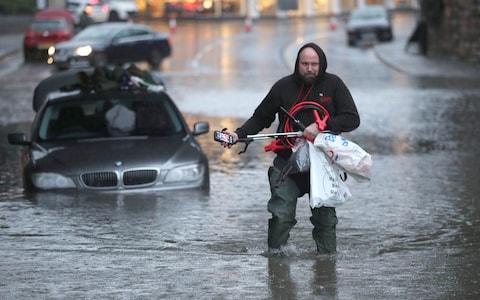 A man wades through a flooded street Sheffield - Credit: PA
