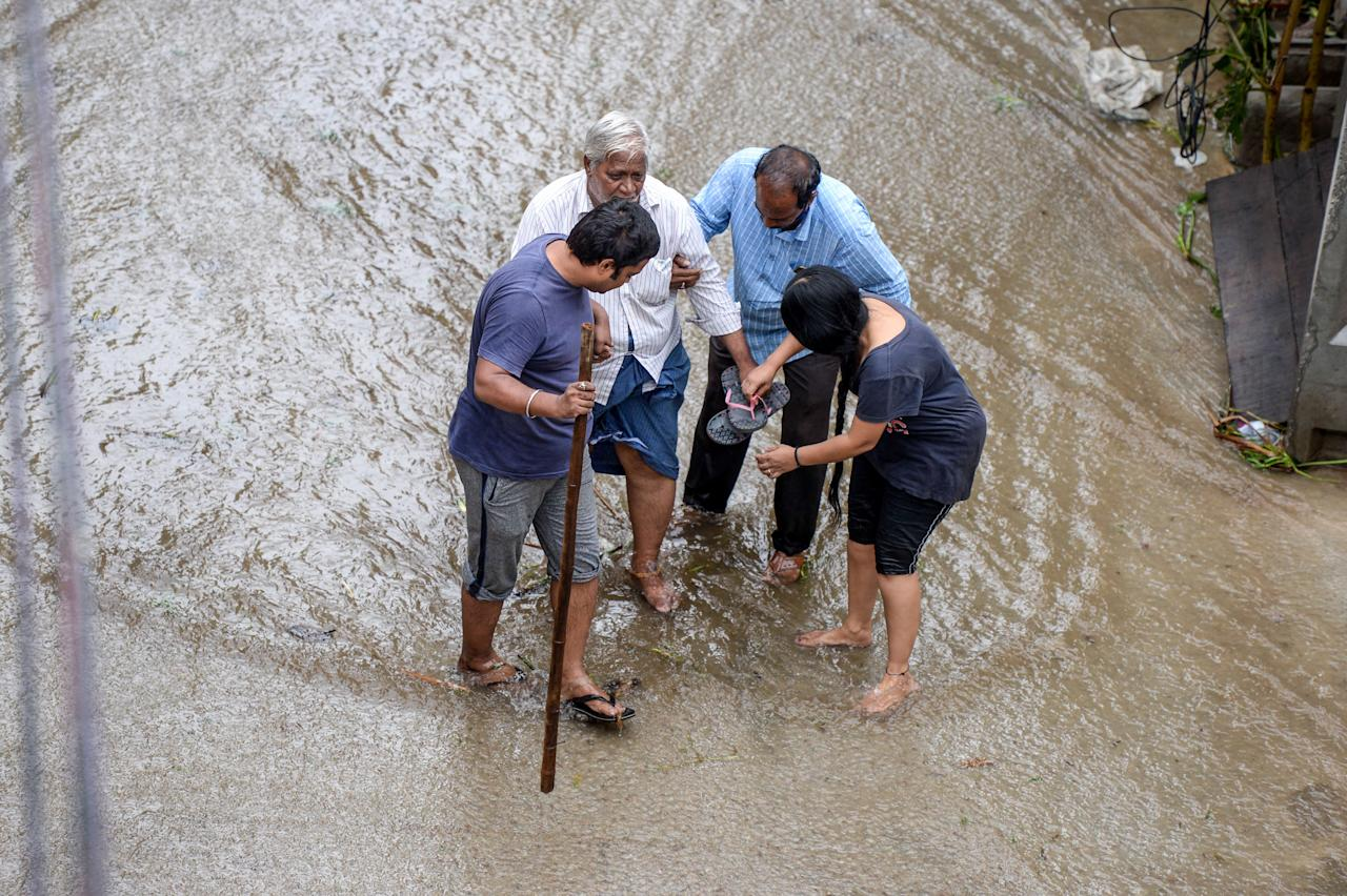 Residents help an elderly man (2L) to make his way on a flooded street following heavy rains in Hyderabad on October 14, 2020. (Photo by NOAH SEELAM / AFP) (Photo by NOAH SEELAM/AFP via Getty Images)