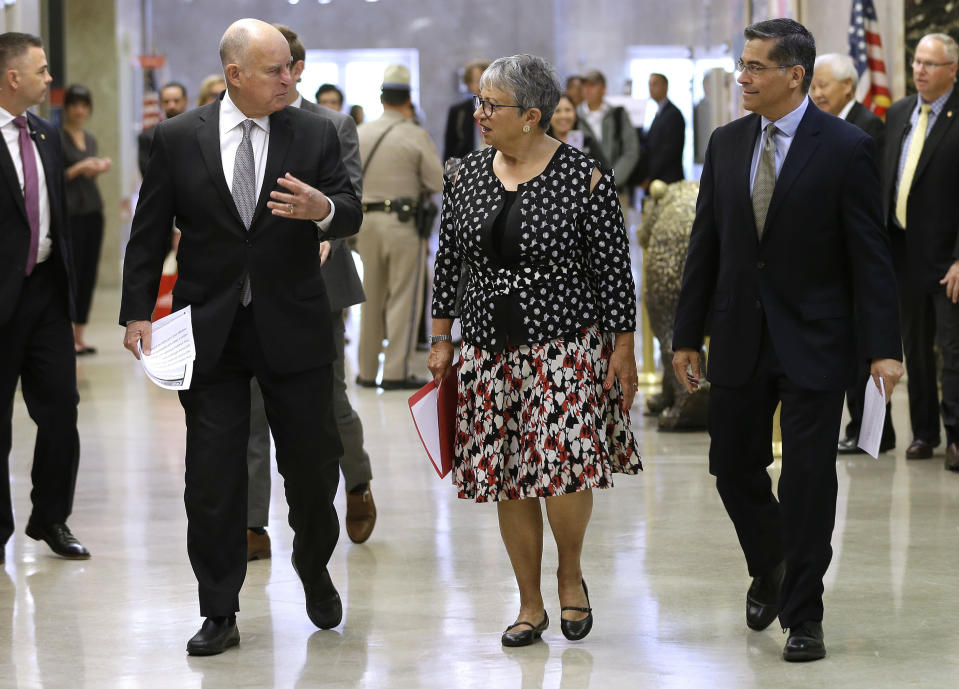 FILE - In this May 1, 2018, file photo, California Gov. Jerry Brown, left, talks with California Air Resources Board Chair Mary Nichols and California Attorney General Xavier Becerra as they walk to a news conference to discuss a lawsuit filed by 17 states and the District of Columbia over the Trump administration's plans to scrap vehicle emission standards, in Sacramento, Calif. Nichols' term leading CARB ends in December 2020. She's held the role since 2007 after an earlier stint as chair in the early 1980s. (AP Photo/Rich Pedroncelli, File)