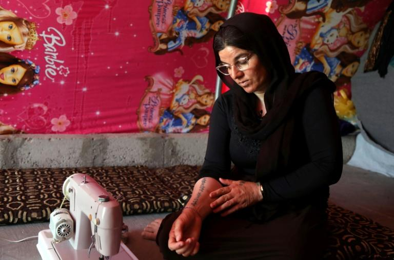 Yazidi survivor Layleh Shemmo looks at a tatoo bearing the names of her two sons at a tent in the Khonke displacement camp in northwestern Iraq on June 24, 2019