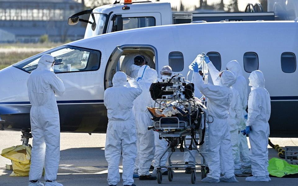 Medical staff load a patient infected with Covid-19 onto a plane for an evacuation, at Nimes-Garon airport in Saint-Gilles, France - AFP