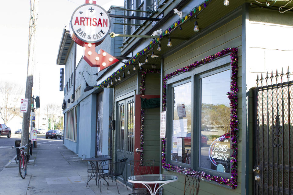 A bike sits outside Artisan Bar and Cafe on St. Claude Avenue on Jan. 30, 2021, in New Orleans. The toll of this year's toned-down Mardi Gras is evident on St. Claude Avenue, an off-the-beaten-track stretch that has become a destination in recent years. (AP Photo/Dorthy Ray)