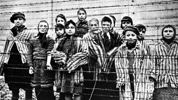 PHOTO: A group of child survivors stand behind a barbed wire fence at the Nazi concentration camp at Auschwitz-Birkenau in southern Poland, on the day of the camp's liberation by the Soviet Army, Jan. 27, 1945. (Galerie Bilderwelt/Getty Images)