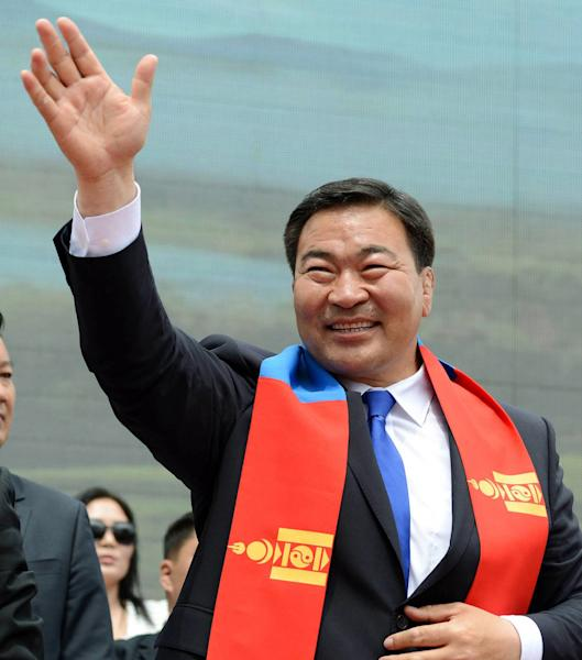 In this Monday, June 24, 2013 photo, opposition Mongolian People's Party lawmaker Baterdene Badmaanyambuu, a former wrestling champion who has portrayed himself as a clean politician committed to upholding national unity and fighting the environmental degradation brought by the mining industry, waves at his supporters during his campaign rally in Ulan Bator, Mongolia, for Wednesday's presidential elections. Baterdene is the main rival to corruption-busting incumbent Elbegdorj Tsakhia, of the ruling Democratic Party, as residents of the vast, landlocked northern Asian nation and strong U.S. ally vote in the elections. (AP Photo/Kyodo News) JAPAN OUT, MANDATORY CREDIT