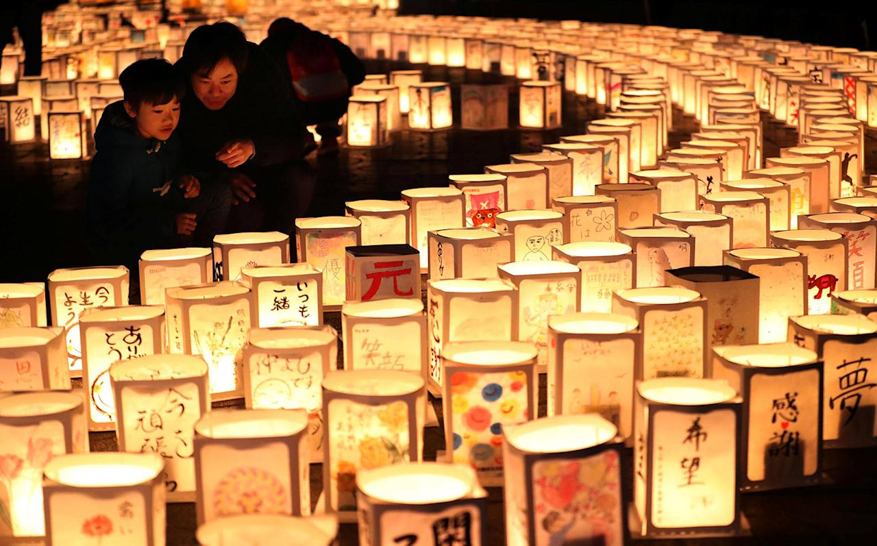 <p>A family looks at paper lanterns during a memorial event to mourn victims of the March 11, 2011 earthquake and tsunami disaster, in Natori, Miyagi prefecture, Japan, in this photo taken by Kyodo March 11, 2017, to mark the six-year anniversary of the disaster that killed thousands and set off a nuclear crisis. (Photo: Kyodo/Reuters) </p>