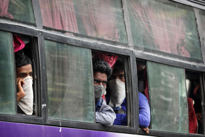 Migrant laborers, returning from other states, many of whom have been walking and hitchhiking, ride in a bus as they try to reach their native villages in Prayagraj, India, Sunday, May 10, 2020. (AP Photo/Rajesh Kumar Singh)