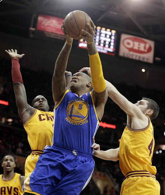 Golden State Warriors' Marreese Speights, center, jumps to the basket against Cleveland Cavaliers' Dion Waiters, left, and Tyler Zeller, right, during the first quarter of an NBA basketball game Sunday, Dec. 29, 2013, in Cleveland. (AP Photo/Tony Dejak)