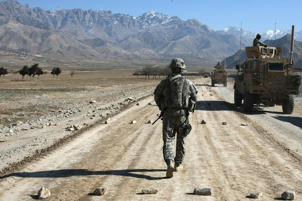 A US soldier from a protection squad for a PRT (Provincial Reconstruction Team) walks along a road under construction near Bagram, about 60 km from Kabul in 2010 (AFP via Getty Images)