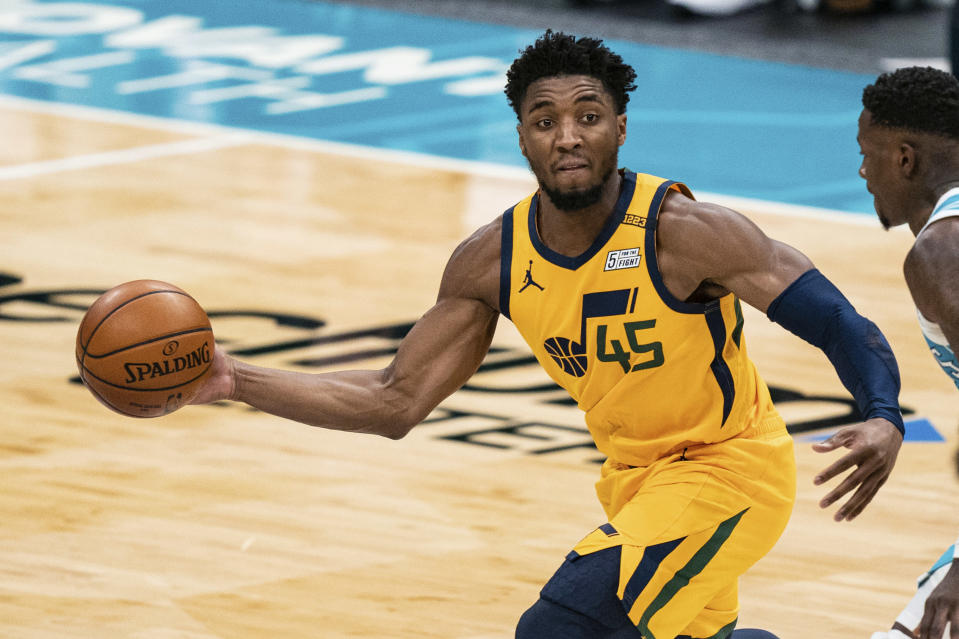 Utah Jazz guard Donovan Mitchell (45) passes the ball while guarded by Charlotte Hornets guard Terry Rozier during the second half of an NBA basketball game in Charlotte, N.C., Friday, Feb. 5, 2021. (AP Photo/Jacob Kupferman)