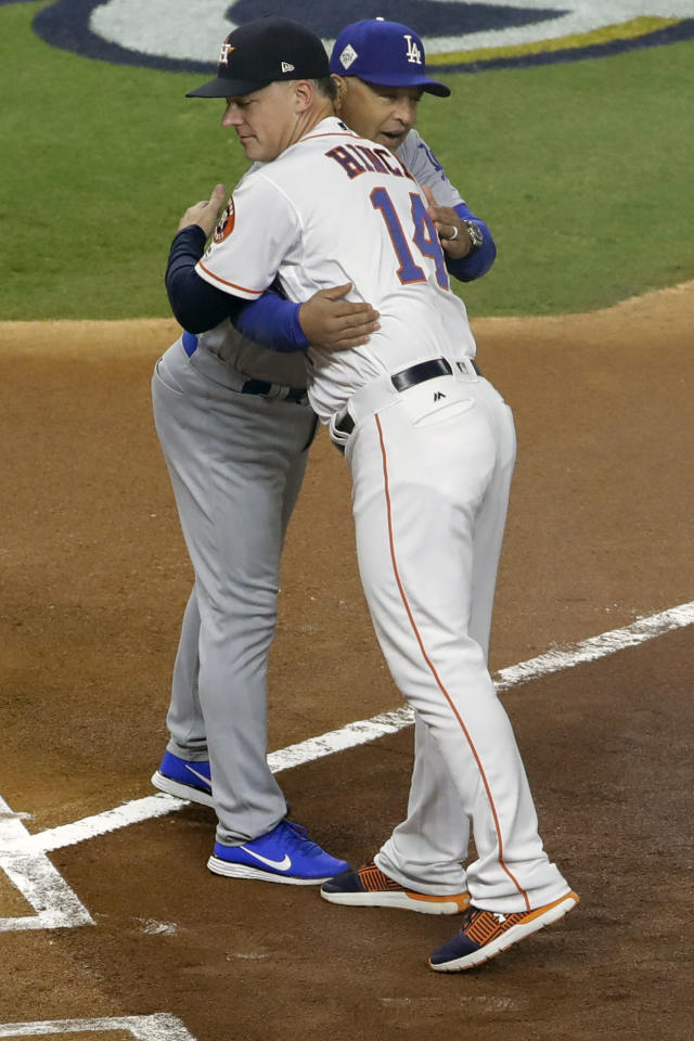 FILE - In this Oct. 27, 2017, file photo, Houston Astros manager A.J. Hinch hugs Los Angeles Dodgers manager Dave Roberts before Game 3 of baseball's World Series in Houston. Houston manager AJ Hinch and general manager Jeff Luhnow were suspended for the entire season Monday, Jan. 13, 2020, and the team was fined $5 million for sign-stealing by the team in 2017 and 2018 season. Commissioner Rob Manfred announced the discipline and strongly hinted that current Boston manager Alex Cora — the Astros bench coach in 2017 — will face punishment later. Manfred said Cora developed the sign-stealing system used by the Astros. (AP Photo/David J. Phillip, File)
