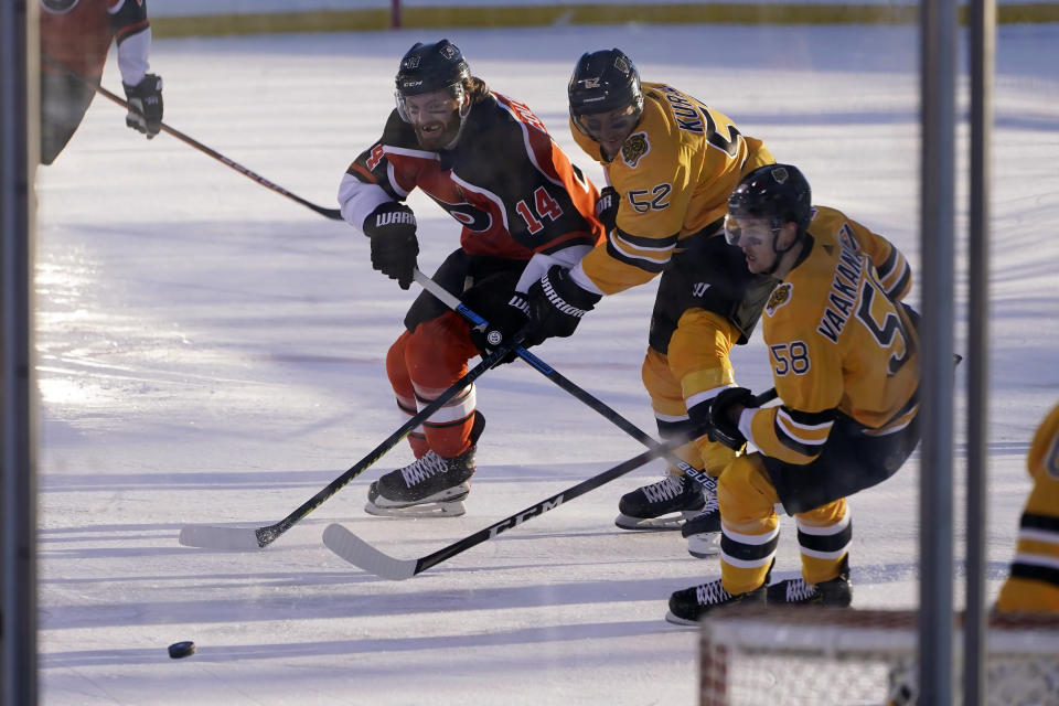 Philadelphia Flyers center Sean Couturier (14) races for the puck against Boston Bruins' Sean Kuraly (52) and Urho Vaakanainen (58) during the first period of an NHL hockey game in Stateline, Nev., Sunday, Feb. 21, 2021. (AP Photo/Rich Pedroncelli)