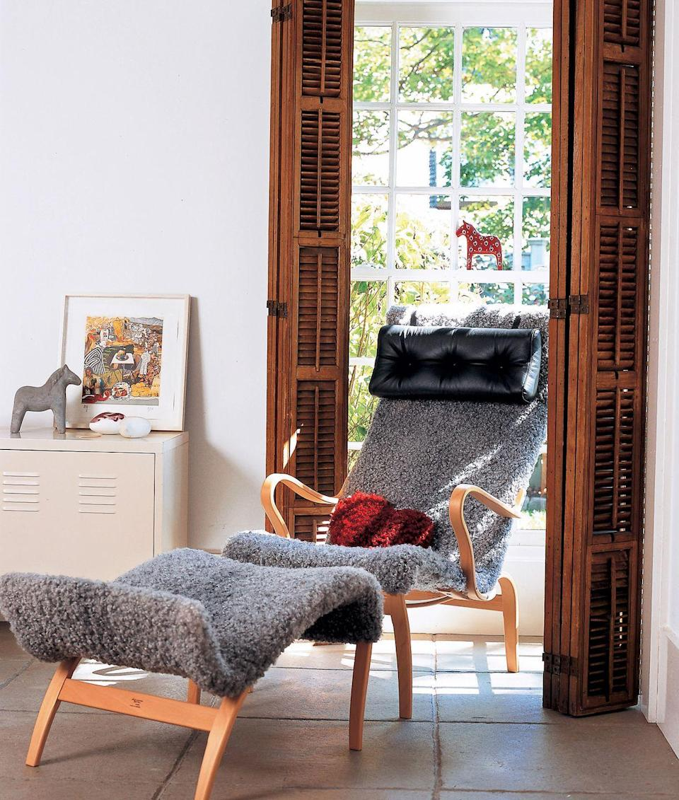 <p>A gray textured chair and complementary foot rest soften the look of this reading nook's wood doors. </p>