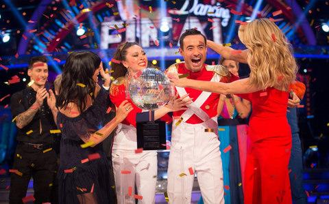 Claudia Winkleman (left) and Tess Daly (right) present Katya Jones and Joe McFadden with the glitterball trophy - Credit: Guy evy BBC/PA