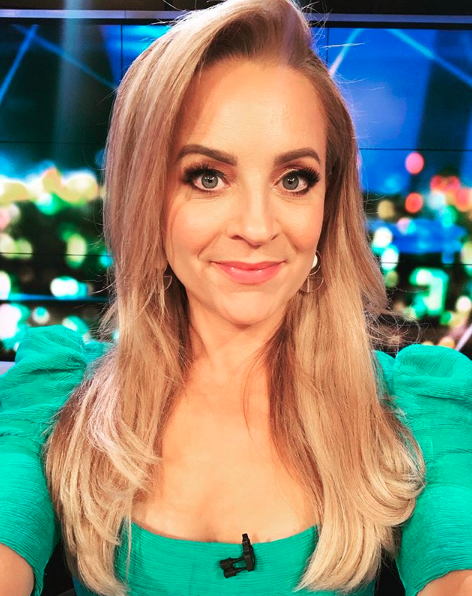 Carrie Bickmore in a green top taking a selfie and smiling at the camera.