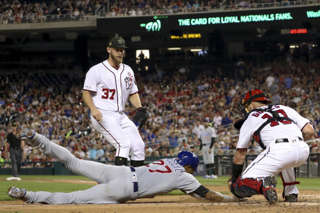 Washington Nationals starting pitcher Stephen Strasburg (37) watches as catcher Yan Gomes (10) tags out Chicago Cubs' Addison Russell (27) who tried to score on a passed ball during the fifth inning of a baseball game Saturday, May 18, 2019, in Washington. (AP Photo/Andrew Harnik)