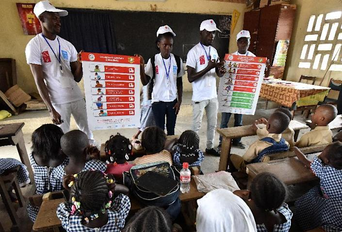 Pupils look at an Ebola prevention poster during a campaign against the Ebola virus by the United Nations Development Programme (UNDP) at a primary school in the popular neighborhood of Koummassi in Abidjan on September 15, 2014 (AFP Photo/Sia Kambou)