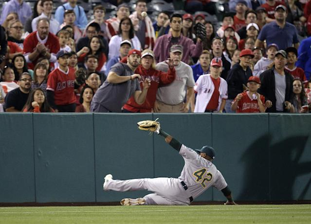 Oakland Athletics' Yoenis Cespedes misses a foul ball hit by Los Angeles Angels' Kole Calhoun during the second inning of a baseball game Tuesday, April 15, 2014, in Anaheim, Calif. (AP Photo/Jae C. Hong)
