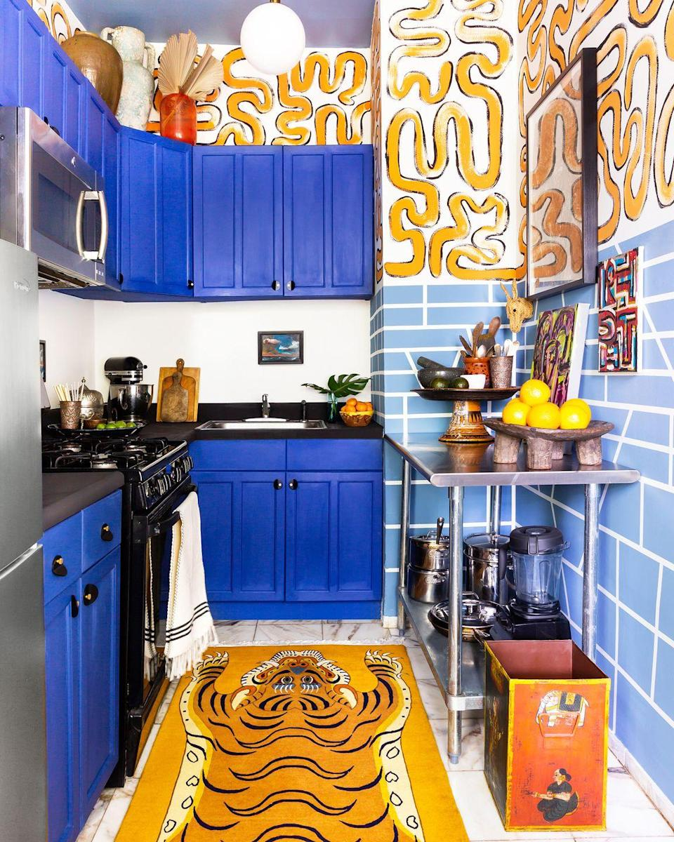 """<p>There's no way you can enter this kitchen and not have fun, even if the task at hand is doing the dishes. The hand-painted orange squiggles, vibrant blue cabinets, and cheeky faux hide area rug give it so much character. See the full kitchen <a href=""""https://www.housebeautiful.com/design-inspiration/home-makeovers/a30080707/kitchen-makeover-only-paint-tape-anthony-gianacakos/"""" rel=""""nofollow noopener"""" target=""""_blank"""" data-ylk=""""slk:here"""" class=""""link rapid-noclick-resp"""">here</a>.</p>"""