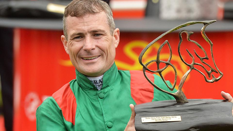 Jockey Pat Smullen is pictured lifting a trophy.