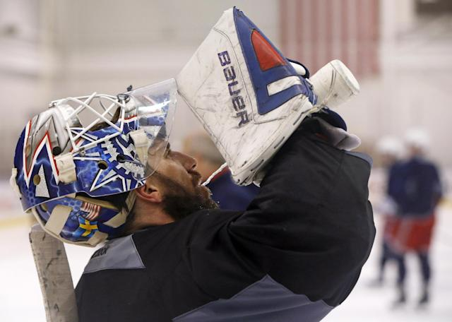 New York Rangers goalie Henrik Lundqvist, of Sweden, drinks water from a squirt bottle during a team practice at the Rangers training facility in Greenburgh, N.Y., Sunday, June 1, 2014. The Rangers have advanced to the Stanley Cup finals. (AP Photo/Kathy Willens)
