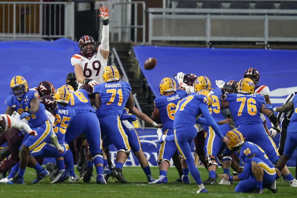 Pittsburgh place kicker Alex Kessman (97), center, hits a field goal as Virginia Tech's Luke Tenuta (69) leaps in an effort to block it during the first half of an NCAA college football game, Saturday, Nov. 21, 2020, in Pittsburgh. (AP Photo/Keith Srakocic)