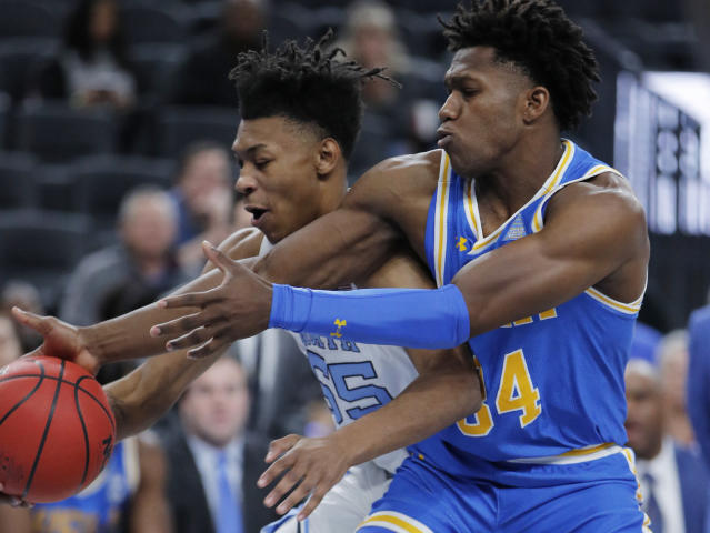 North Carolina's Christian Keeling, left, and UCLA's David Singleton battle for the ball during the first half of an NCAA college basketball game Saturday, Dec. 21, 2019, in Las Vegas. (AP Photo/John Locher)