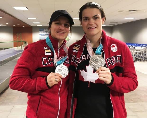 Nova Scotia's only 2018 Olympians Jillian Saulnier, left, and Blayre Turnbull, right, show off their Olympic silver medals at the Halifax Stanfield International Airport in February 2018. They both hope to bring home gold if they're named to the 2022 Olympic squad. (Marina von Stackelberg/CBC - image credit)