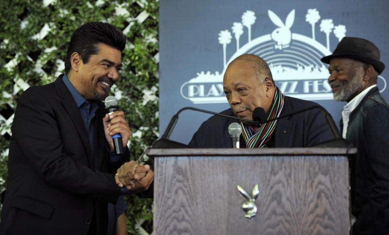 Musician Quincy Jones, center, joins hands with new Playboy Jazz Festival master of ceremonies George Lopez, left, at a news conference at the Playboy Mansion on Thursday, Feb. 28, 2013 in Los Angeles. Looking on at right is jazz musician Hubert Laws. The 35th Anniversary Playboy Jazz Festival will be held at the Hollywood Bowl on June 15 and 16. (Photo by Chris Pizzello/Invision/AP)