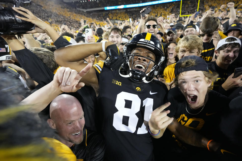 Iowa wide receiver Desmond Hutson (81) celebrates with fans on the field after Iowa beat Penn State 23-20, in an NCAA college football game, Saturday, Oct. 9, 2021, in Iowa City, Iowa. (AP Photo/Matthew Putney)