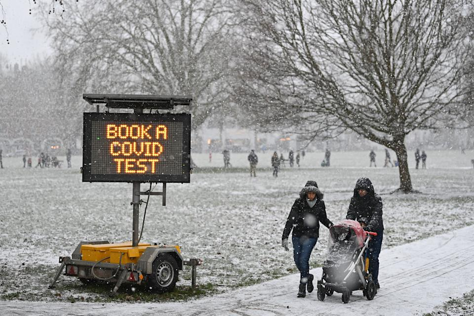 A sign advising people to get a covid-19 test is displayed in a park as snow falls in west London on January 24, 2021, as the capital experiences a rare covering of snow on Sunday. (Photo by DANIEL LEAL-OLIVAS / AFP) (Photo by DANIEL LEAL-OLIVAS/AFP via Getty Images)