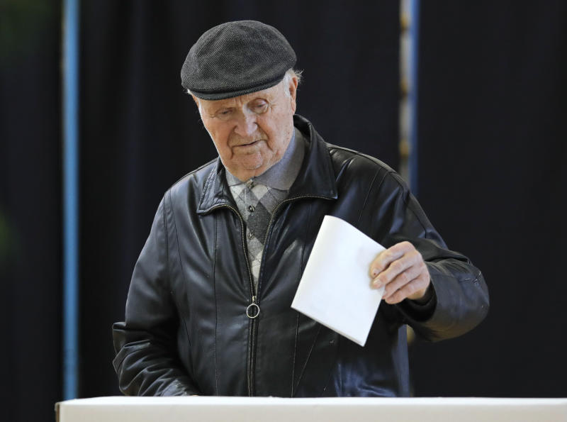 A man casts his vote in Bucharest, Romania, Sunday, Nov. 10, 2019. Voting got underway in Romania's presidential election after a lackluster campaign overshadowed by a political crisis which saw a minority government installed just a few days ago. (AP Photo/Vadim Ghirda)