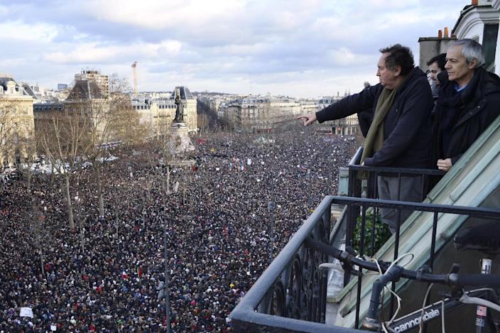 Residents watch from a balcony as thousands of people taking part in a unity rally on the Place de la Republique in Paris on January 11, 2015 (AFP Photo/Bertrand Guay)
