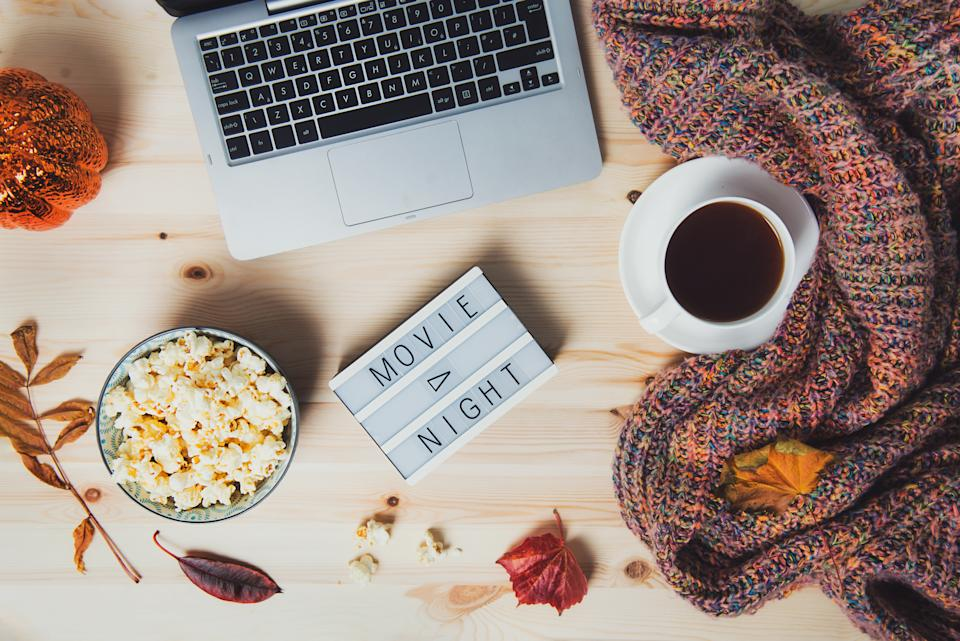 Top view Movie night concept. Flat lay composition with Movie night message on the board, laptop, popcorn bowl, decorative pumpkin, fallen leaves, a cup of tea, and warm plaid on wooden background