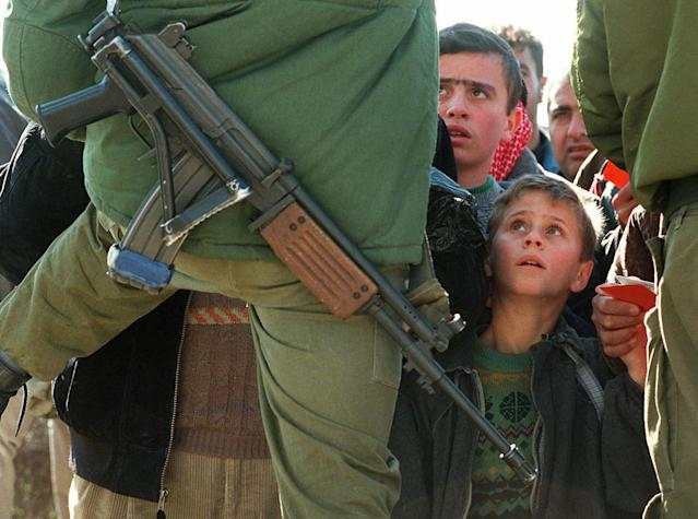 <p>A Palestinian boy clings to the hand of his father, who is holding his identity card, and looks up at an Israeli soldier armed with a Galil assault rifle at the Bethlehem checkpoint in southern Jerusalem, Jan. 9, 1998. (Photo: Jacqueline Larma/AP) </p>