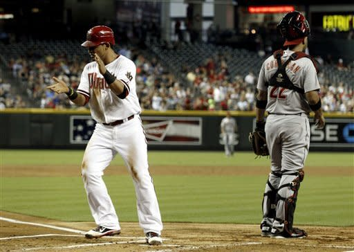 Arizona Diamondbacks' Gerardo Parra, left, applauds as he scores a run in front of Houston Astros' Carlos Corporan during the first inning in a baseball game on Friday, July 20, 2012, in Phoenix. (AP Photo/Ross D. Franklin)