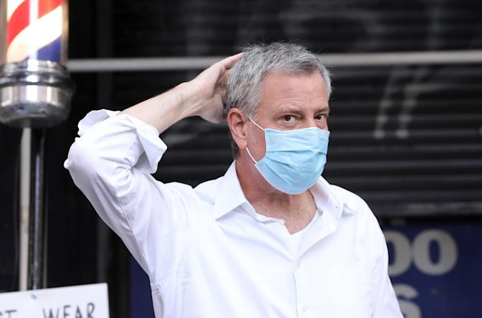 New York City Mayor Bill de Blasio jokingly smooths his new haircut at Astor Place Hairstyles during the phase two re-opening of businesses following the outbreak of the coronavirus disease (COVID-19) in New York City, New York, U.S., June 23, 2020. REUTERS/Caitlin Ochs