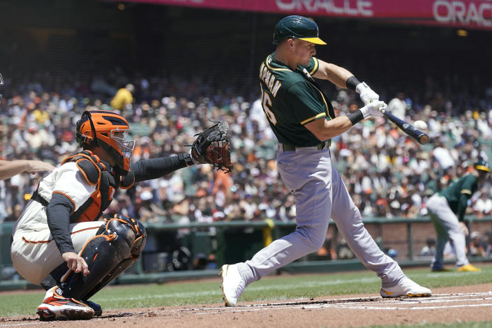 Oakland Athletics' Matt Chapman, right, hits a two-run single in front of San Francisco Giants catcher Buster Posey during the first inning of a baseball game in San Francisco, Sunday, June 27, 2021. (AP Photo/Jeff Chiu)