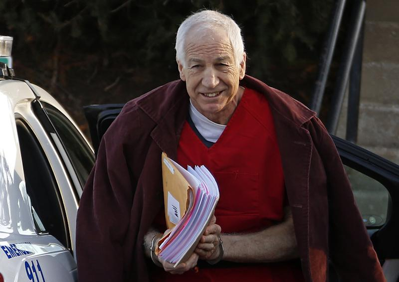 FILE - In this Jan. 10, 2013, file photo, former Penn State assistant football coach Jerry Sandusky arrives at the Centre County Courthouse for a post-sentencing hearing in Bellefonte, Pa. Penn State said Monday, Oct. 28, 2013 that it is paying $59.7 million to 26 young men over claims of child sexual abuse at the hands of Sandusky. The university said it had concluded negotiations that have lasted about a year. The school said 23 deals are fully signed and three are agreements in principle. The school faces six other claims, and the university says it believes some do not have merit while others may produce settlements. Sandusky, 69, is serving a 30- to 60-year prison sentence at a state prison in southwestern Pennsylvania. (AP Photo/Gene J. Puskar, File)