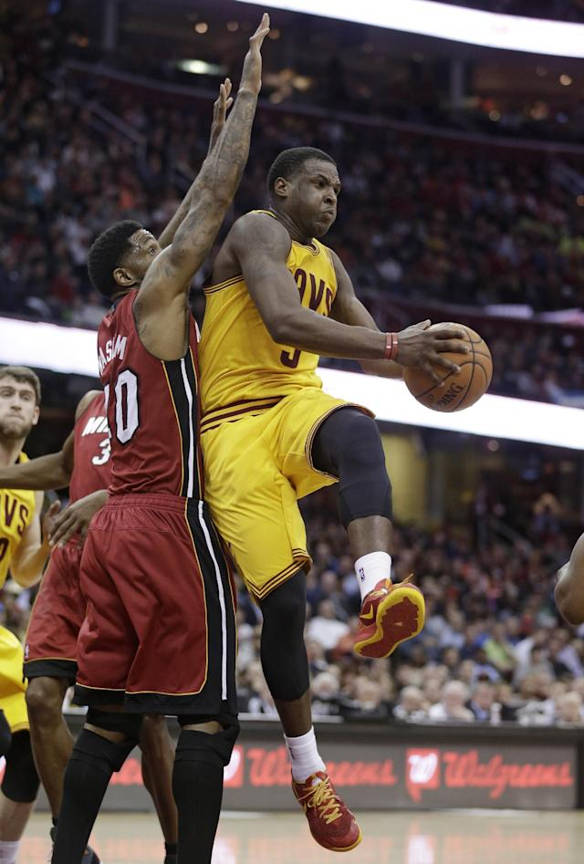 Cleveland Cavaliers' Dion Waiters, right, looks to pass to a teammate under pressure from Miami Heat's Udonis Haslem during the second quarter of an NBA basketball game Tuesday, March 18, 2014, in Cleveland. (AP Photo/Tony Dejak)