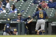 Milwaukee Brewers' Kolten Wong (16) celebrates with manager Craig Counsell left, at the dugout after hitting a solo home run during the sixth inning of a baseball game against the Chicago Cubs, Friday, April 23, 2021, in Chicago. (AP Photo/Paul Beaty)