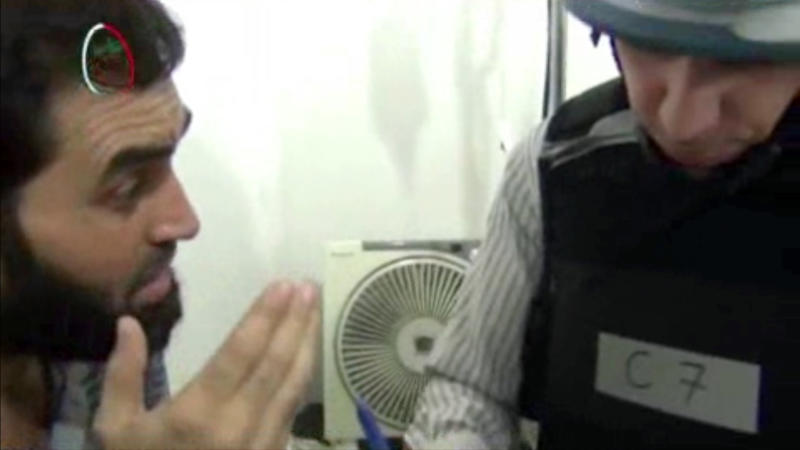 ADDS DATE IMAGE WAS TAKEN, REMOVES REFERENCE TO UNVERIFIED IMAGE - In this Monday, Aug. 26, 2013 image taken from amateur video footage provided by the Media Office Of Moadamiyeh, a UN inspector, right, speaks to a man about the alleged chemical weapon attack as a UN inspection team visits a makeshift hospital in Moadamiyeh, a suburb of the Syrian capital of Damascus. Doctors Without Borders said 355 people were killed in an artillery barrage by regime forces on Wednesday, Aug. 21, 2013 that included the use of toxic gas. The media office of Moadamiyeh is a loosely organized Anti-Assad activist group based in Moadamieyh which posts video and still images of violence and other developments from the region. (AP Photo/Media Office Of Moadamiyeh)