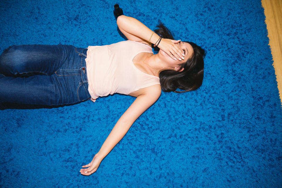 Young woman wearing blue jeans and a pink tank top lying on her back on the floor laughing with a hand over her mouth