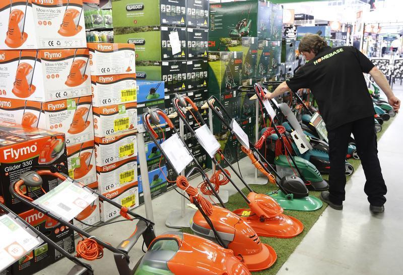 A sales assistant works on a display of lawnmowers at a Homebase store in Aylesford in south east England